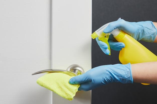 Kobiece dłonie dezynfekują i myją klamki do drzwi zapobieganie koronawirusowi podczas covid19