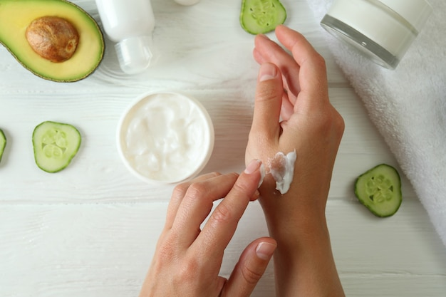 Kobiece dłonie i naturalne kosmetyki spa na białym drewnianym stole