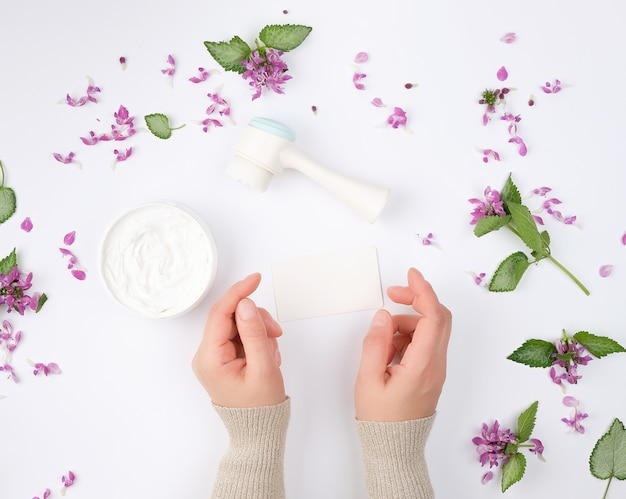 Kobiece dłonie i słoik z gęstą śmietaną i różowymi kwiatami z zielonymi liśćmi