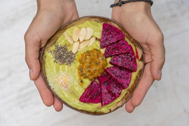 Kobiece dłonie i zielony koktajl z awokado w kokosowej misce z owocami smoka, marakują, płatkami migdałów, chipsami kokosowymi i nasionami chia na śniadanie. pojęcie zdrowego odżywiania, pożywienie. bali, indonezja