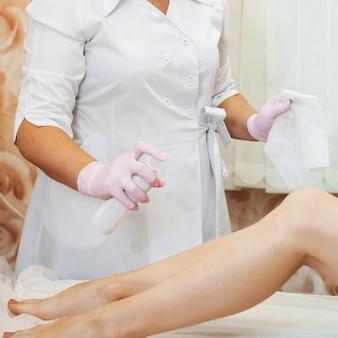 Kobiece dłonie kosmetyczki przygotowujące szczupłe kobiece nogi do zabiegu usuwania włosów z cukru