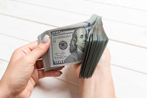 Kobiece dłonie liczenia pieniędzy na drewniane tła
