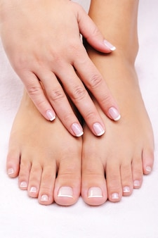 Kobiece dłonie na zadbanych stopach z francuskim pedicure