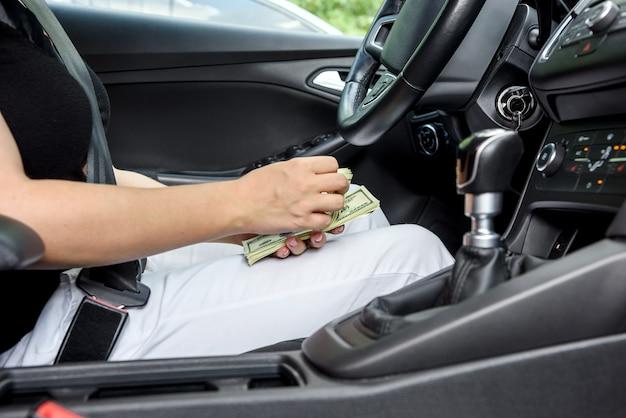 Kobiece dłonie oferują pakiet dolar. kobieta kierowca daje łapówkę