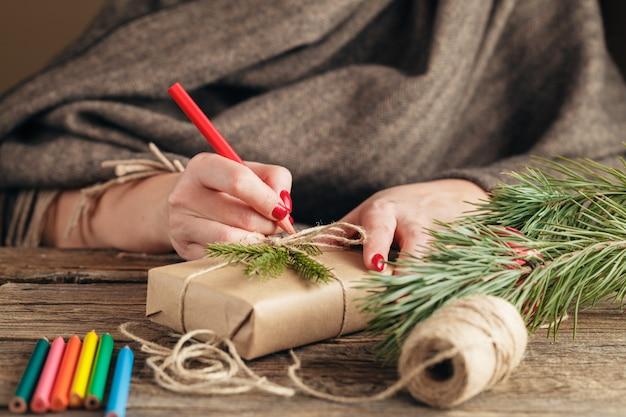 Kobiece dłonie owijające święto bożego narodzenia ręcznie robione w papier rzemieślniczy ze wstążką sznurka wykonywanie kokardki w świątecznym pudełku ozdobionym płatkiem śniegu. nożyce na białym drewnianym stole