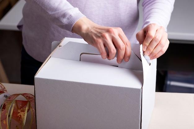 Kobiece dłonie pakują prezent w biały kartonik. opakowania cukiernicze. ścieśniać