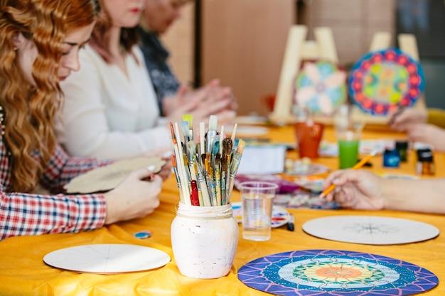 Kobiece dłonie pędzle i farby z bliska czerpią z treningu artystycznego, aby stworzyć mandalę życia