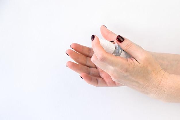 Kobiece dłonie pokazują, jak używać antybakteryjnego sprayu
