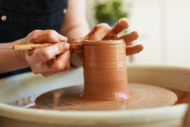 Kobiece dłonie pracują z surową gliną na kole garncarskim. mistrzowska klasa robienia dzbanka.
