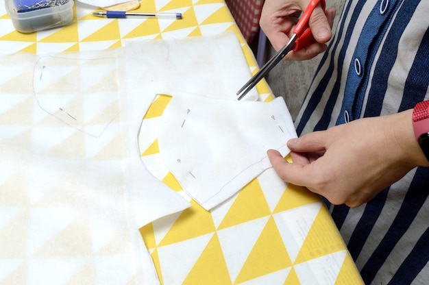 Kobiece dłonie przecinają materiał nożyczkami według wzoru na stole.