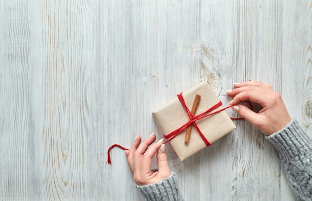 Kobiece dłonie przygotowują prezenty świąteczne i noworoczne do pakowania prezentów świątecznych na jasnym drewnianym stole. prezenty dla krewnych i przyjaciół z gratulacjami