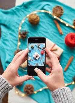 Kobiece dłonie robią zdjęcie na smartfonie kompozycji noworocznej z góry. twórz i pakuj boże narodzenie i prezenty na święta. prezenty dla krewnych i przyjaciół z gratulacjami