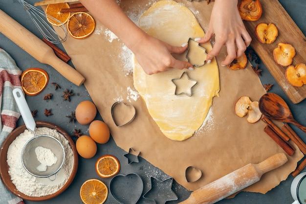 Kobiece dłonie robiące ciasteczka ze świeżego ciasta w domu