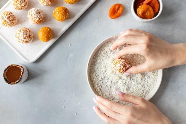 Kobiece dłonie robiące wegańskie kulki energetyczne zdrowe wegańskie jedzenie