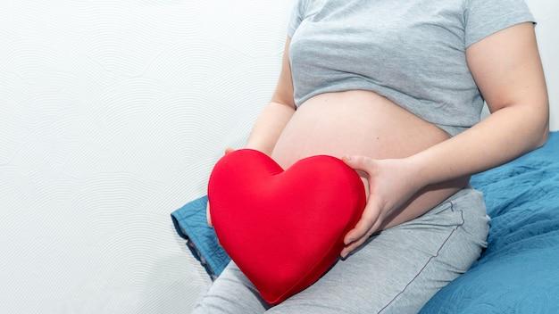 Kobiece dłonie trzymają czerwoną poduszkę w kształcie serca