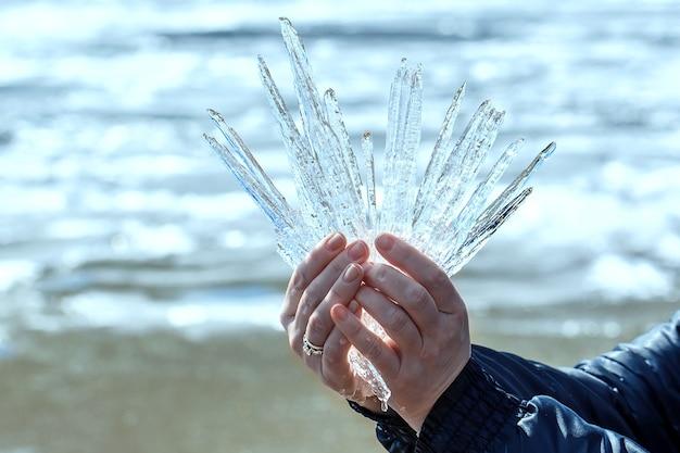 Kobiece dłonie trzymają kryształowy blok lodu z topniejącego śniegu. ostatni lód na wołdze