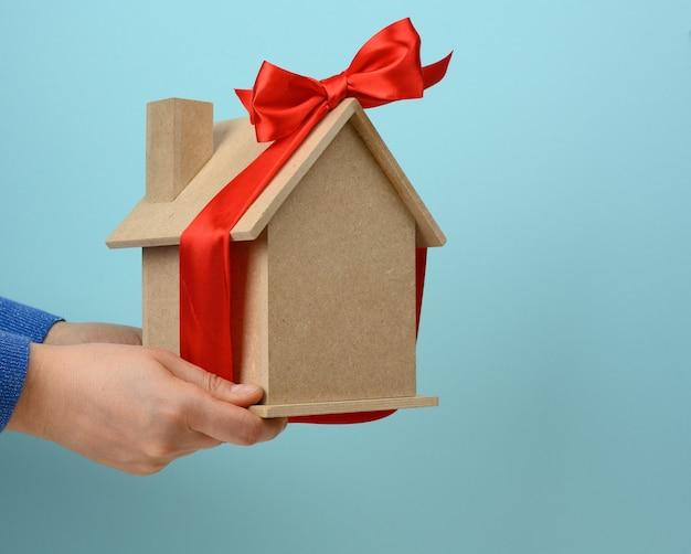 Kobiece dłonie trzymają model drewnianego domu zawiązanego czerwoną jedwabną wstążką na niebieskiej powierzchni, koncepcja zakupu nieruchomości, hipoteka