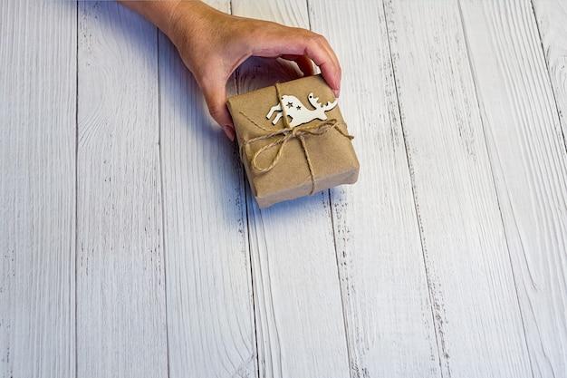 Kobiece dłonie trzymają ręcznie zdobione pudełko na prezenty świąteczne lub noworoczne. jasne drewniane tła.