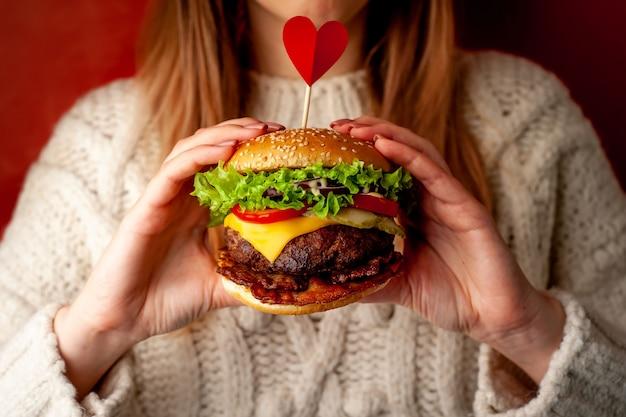 Kobiece dłonie trzymają smacznego domowego burgera