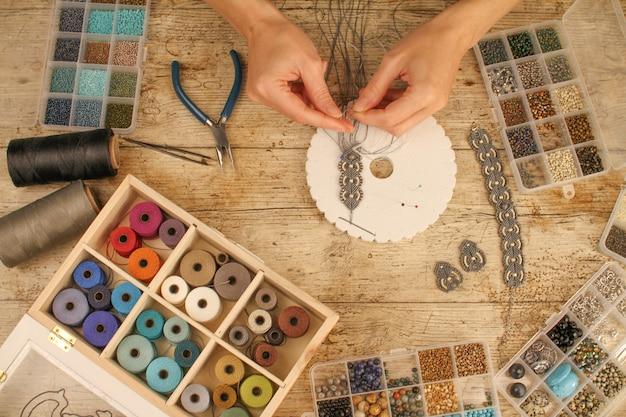 Kobiece dłonie tworzące bransoletę makramé