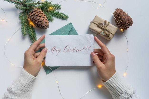 Kobiece dłonie, ubrane w biały sweter, trzymające kartkę białego papieru z napisem merry christmas.