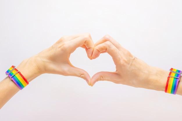 Kobiece dłonie w bransoletce w kolorach tęczy lgbt składane w kształcie serca