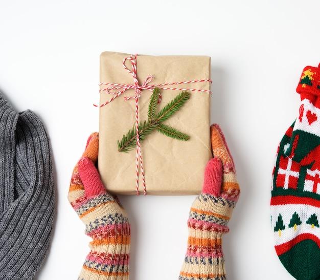 Kobiece dłonie w dzianinowych rękawiczkach trzymają pudełko zawinięte w brązowy papier i przewiązane liną na białym, widok z góry