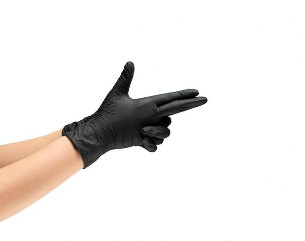Kobiece dłonie w gumowych rękawiczkach ochronnych w czarnym kolorze przedstawiają broń symbol broni.