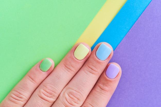 Kobiece dłonie w jasnych kolorach na kolorowym tle