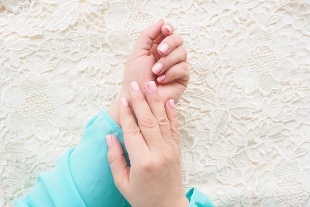 Kobiece dłonie w niebieskiej bluzce z pięknym manicure i delikatnym różowym lakierem do paznokci na beżowej koronkowej tkaninie