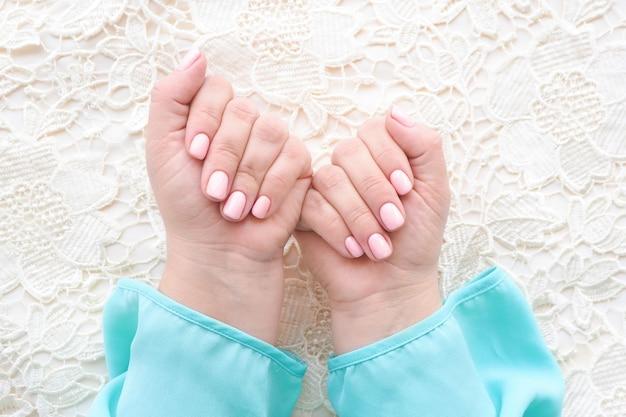 Kobiece dłonie w niebieskiej bluzce z pięknym manicure i delikatnym różowym lakierem do paznokci na beżowym materiale.