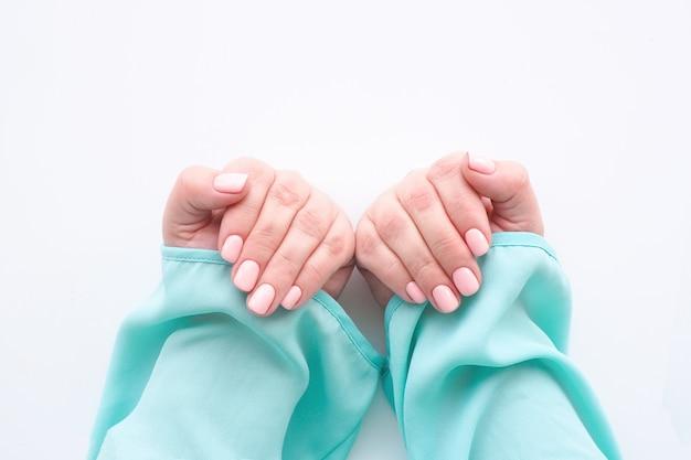 Kobiece dłonie w niebieskiej bluzce z pięknym manicure i delikatnym różowym lakierem do paznokci na białym tle
