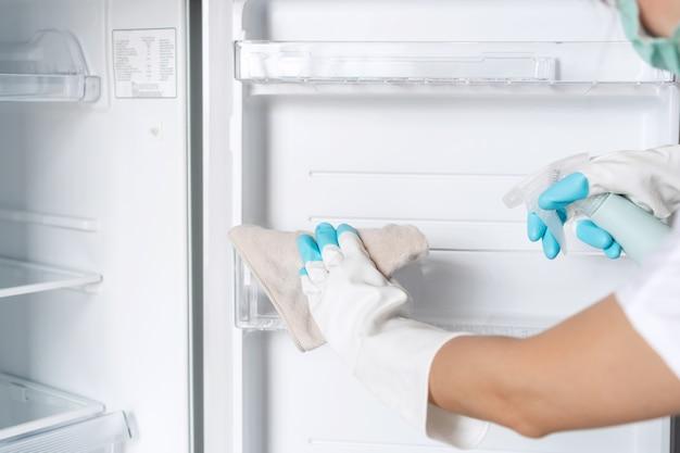 Kobiece dłonie w rękawiczkach czysta pusta lodówka z rozpylaczem i szmatą