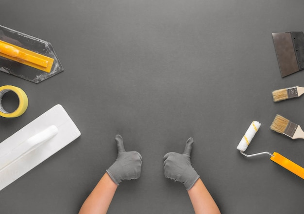 Kobiece dłonie w rękawiczkach pokazujące kciuki do góry na szarym tle z narzędziami do remontu domu.