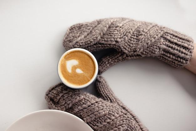 Kobiece dłonie w rękawiczkach trzymają kubek kawy obok na białym stole z bliska