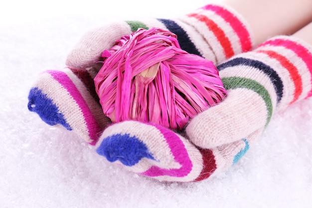 Kobiece dłonie w rękawiczkach z sercem na śniegu