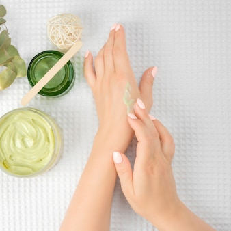 Kobiece dłonie w trakcie rozprowadzania kremu i słoika naturalnego kremu na białych ręcznikach. kobieta ręce stosując krem nawilżający do jej skóry. piękne kobiety ręce na białym ręczniku. widok z góry