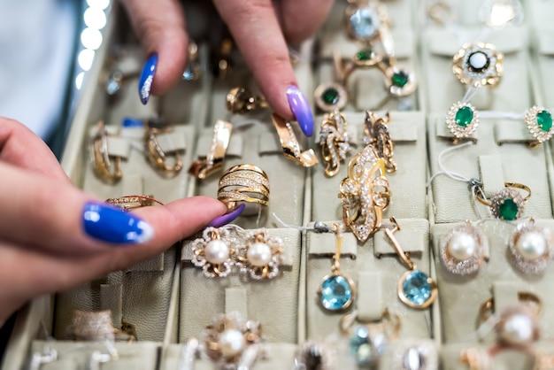 Kobiece dłonie wyświetlono złoty pierścionek na kolekcji biżuterii