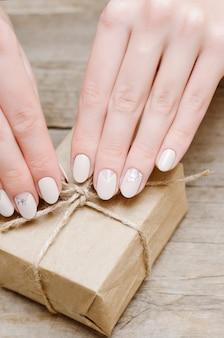 Kobiece dłonie z beżowym wzorem paznokci