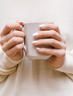 Kobiece dłonie z białym wzorem paznokci.