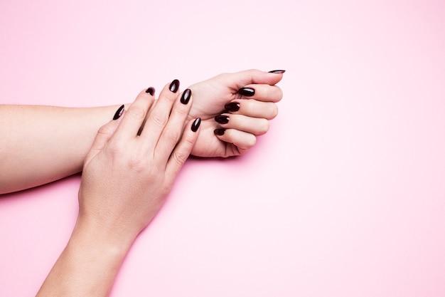 Kobiece dłonie z bordowym manicure na na białym tle różowym.