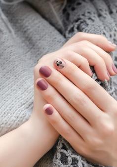 Kobiece dłonie z ciemnoróżowym wzorem do paznokci