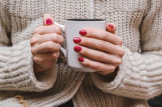 Kobiece dłonie z ciemnoróżowym wzorem do paznokci.