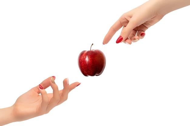 Kobiece dłonie z czerwonym i złotym lakierem do paznokci. stworzenie koncepcji człowieka z dojrzałym jabłkiem na białym tle na białej powierzchni.