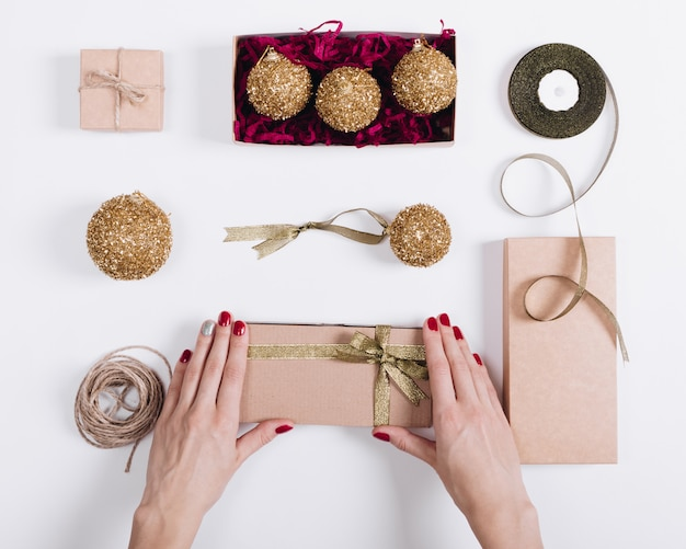 Kobiece dłonie z czerwonym manicure'em przygotowują pudełkowe prezenty na święta