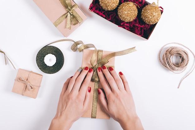 Kobiece dłonie z czerwonym manicure pakują pudełka z prezentami