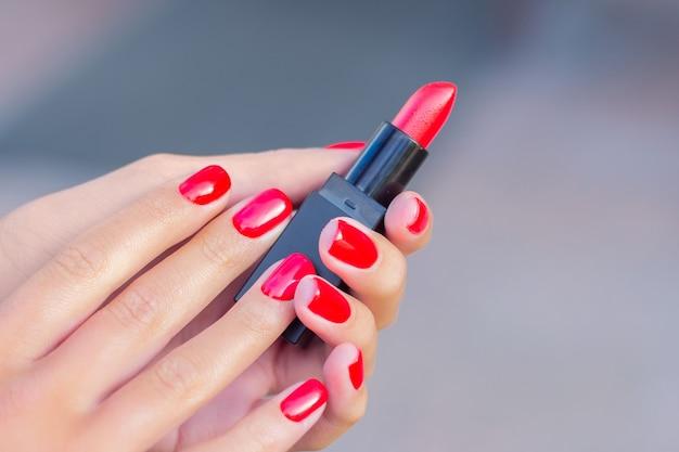 Kobiece dłonie z czerwonymi paznokciami do manicure, trzymając szminkę