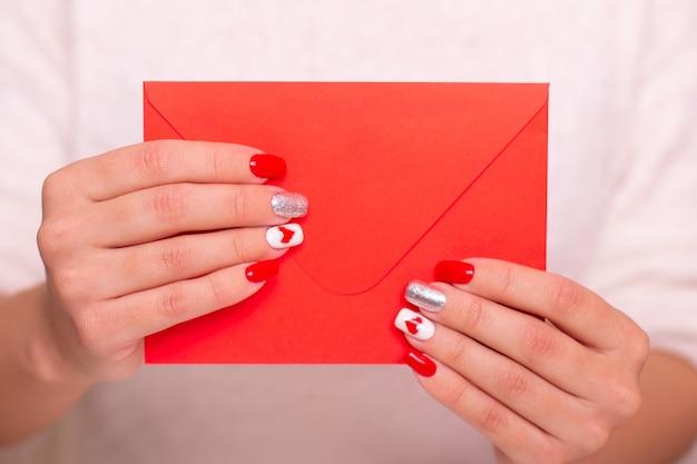 Kobiece dłonie z czerwonymi paznokciami manicure w kształcie serca