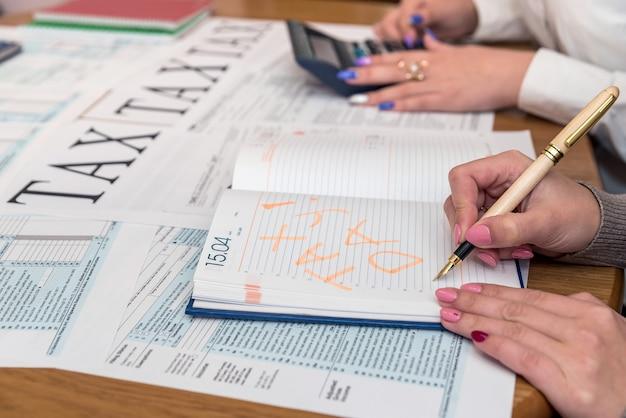 Kobiece dłonie z długopisem i kalkulatorem na formularzu 1040