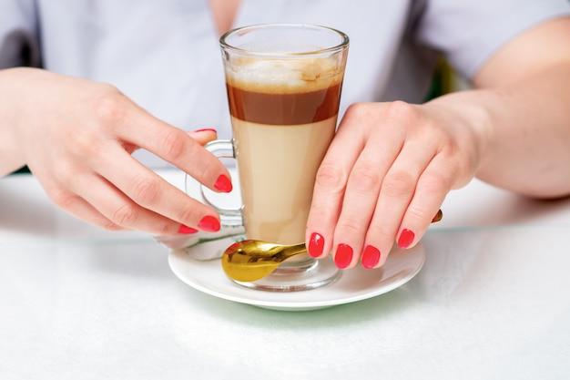 Kobiece dłonie z doskonałym czerwonym manicure trzyma filiżankę kawy cappuccino z bliska.